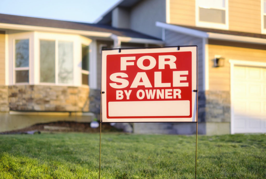 A close up of a For Sale By Owner sign, with a two-story house in the out of focus background.